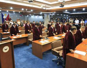 Philippine senators stand in prayer before voting in the impeachment trial of Supreme Court Chief Justice Corona in Manila