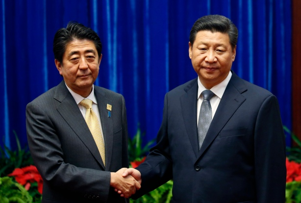 Japan's Prime Minister Shinzo Abe, left, and China's President Xi Jinping, right, shake hands during their meeting at the Great Hall of the People, on the sidelines of the Asia Pacific Economic Cooperation (APEC) meetings, in Beijing, Monday, Nov. 10, 2014. President Xi and Prime Minister Abe held an ice-breaking meeting Monday on the sidelines of an Asia-Pacific conference in Beijing, following more than two years of deep tensions over an island dispute. (AP Photo/Kim Kyung-Hoon, Pool)